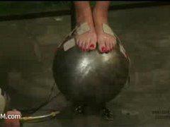 a pain slut is balancing on an overheated steel ball