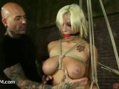 A busty blond whore suspended and fucked by a rock star