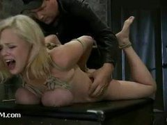 A big-titted blonde gets gagged, hogtied and fingered