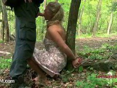 Luscious blonde restrained with an iron brace outdoors
