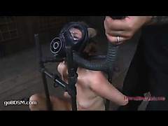A hot slut in a gas mask restrained with belts and tortured viciously