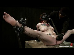A fiery redhead trying to control herself while chained down onto a sybian