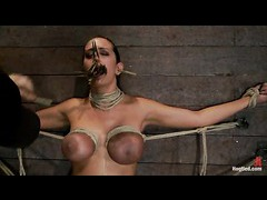 A big titted babe bound to the wall in a frog tie and face fucked