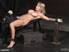 Voluptuous blonde slave gives lusty deepthroating while riding on a powerful sybian