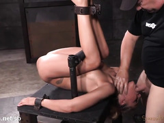 Demure slave in bondage gets simultaneous hammering for her cunt and mouth