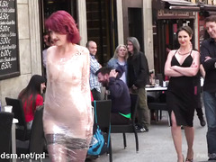 Redhead slave is paraded in public with her naked body wrapped with clingfilm