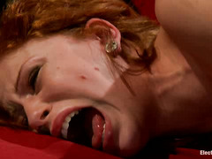 A lovely redhead jumps and twitches as electricity runs through her body