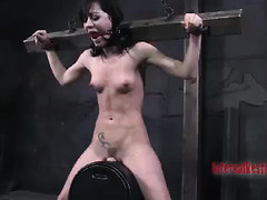 A petite brunette takes pleasure and pain during hard BDSM session