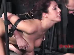 A brunette chick restrained in metal takes a dick down her throat