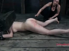 A pretty girl is held down by wood and chains while spanked and caned