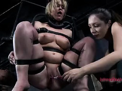 A short-haired, bound slut is caned while another Dom fucks her