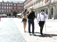 Nearly nude Carol Vega is pulled around on a leash in a city square
