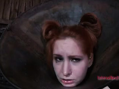 A redhead in a barbaric collar is punished by two relentless Doms