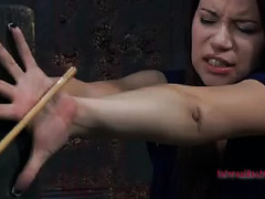 A brunette with long fingernails is restrained in a terrifying and bizarre way