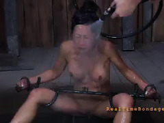 A humiliated and bound sub has piss and hot wax poured onto her body