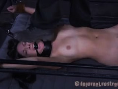 A strapped-down beauty is forced to fuck a thick dildo while whipped