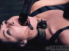 A woman in chains can't see as a shock stick comes near her body