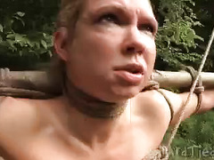 A captive and bound woman is tormented while deep in the woods