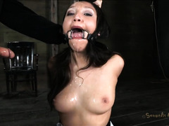 A bound brunette's mouth is stuffed full of her Master's thick cock