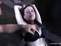 A restrained chick whines as clamps attach firmly to her skin