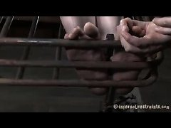 A brunette sub's poor feet are tortured while she's stuck in a cage