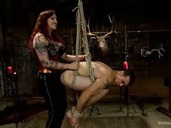 Voluptuous redhead dominatrix makes tattooed stud groans with submission