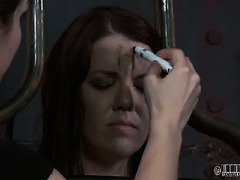 Attractive brunette receives a cold ice punishment in her suspended cage