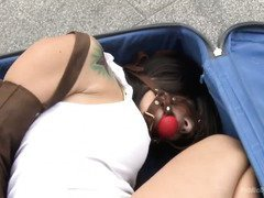 Petite babe is placed inside a luggage bag before receiving rough public sex