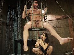 Sultry mistress is giving caged and submissive stud a zealous anal pounding session