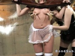Blonde shackled in wooden restraints punished in femdom