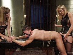 Handsome stud is punished by a stunning mother and daughter in a dungeon