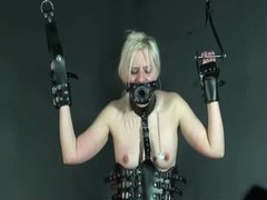 A nasty slut in a leather hood and corset gets tortured