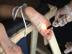 A fully clothed girl takes brutal feet tortures