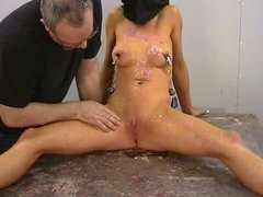 A blindfolded hottie gets her nipples clamped and covered with wax