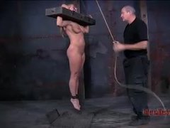A busty blonde gets locked in wooden stocks for tits and pussy tortures