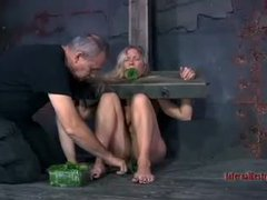 A submissive blonde gets locked in wooden stocks and suspended