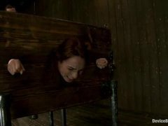 A hot slut is locked in wooden stocks for anal fisting
