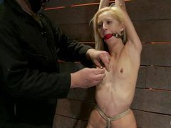 A skinny blonde caned and whipped in predicament bondage