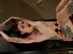 An inked hottie drilled with an electrical strap-on cock