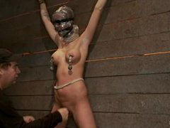 A tight bodied blonde spread against the wall with a diabolical crotch rope
