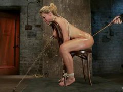 A dazzling babe gets throat fucked while bound on a chair