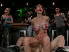 a big-titted brunette with a charming smile is brutally humiliated in a bar full of srangers