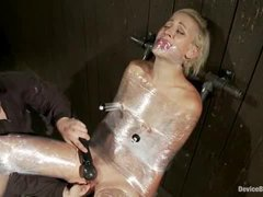 A slim blonde wrapped in plastic and machine fucked