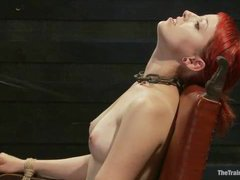 A busty redhead trained to hold composure during punishments