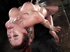 Suspended redhead experiences rough fingering and toying for her pussy